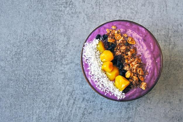 Ciotola di acai colorato luminoso con muesli e frutta secca.