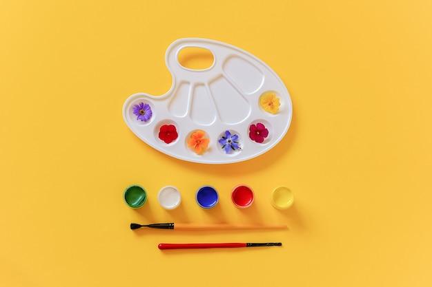 Fiori colorati luminosi su tavolozza artistica, pennello e tempera