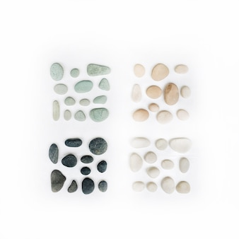 Collezione di pietre pastello colorate luminose. pietre menta, rosa, beige e grigie su fondo bianco