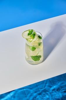 Cocktail fresco e luminoso con menta di cetriolo e cubetti di ghiaccio a bordo piscina