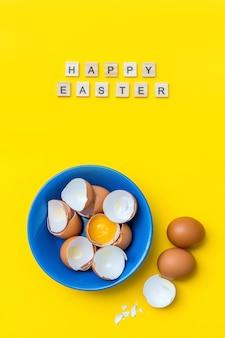 Cartolina creativa luminosa con testo di buona pasqua. uova crude, tuorlo e guscio in un piatto blu su una superficie gialla