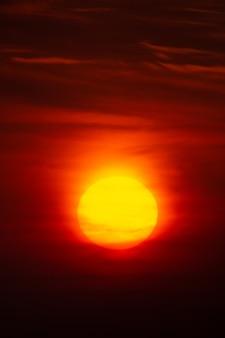 Sole cremisi brillante su uno sfondo di tramonto o alba