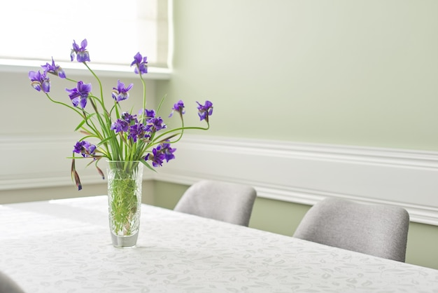 Luminosa sala da pranzo interna, tavolo e sedie vicino alla finestra, bouquet di iridi viola in vaso, spazio tovaglia bianca, spazio di copia