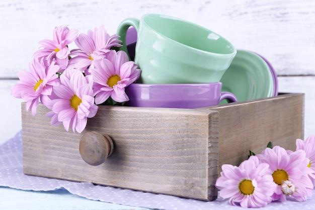 Piatti luminosi con fiori in cassa sulla tavola di legno