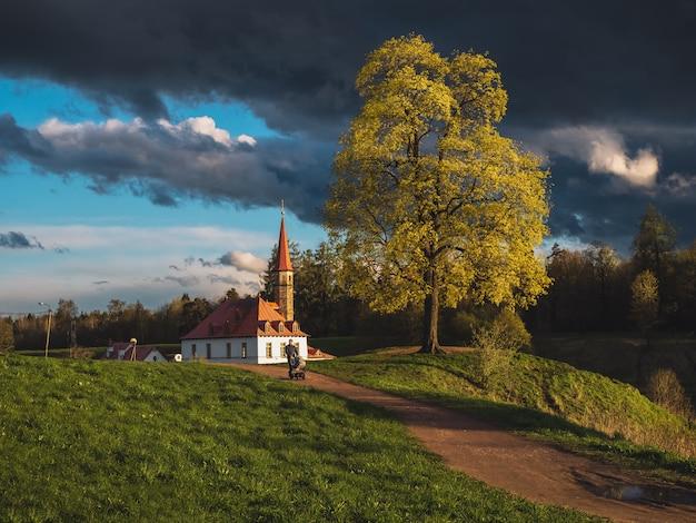 Luminoso paesaggio drammatico con il vecchio castello al tramonto e un uomo che cammina con un passeggino