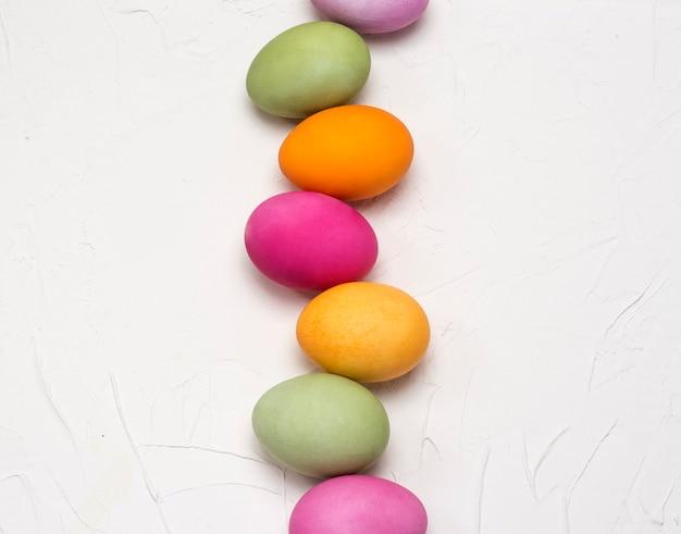 Il piatto luminoso delle uova di pasqua giaceva in fila su uno sfondo bianco con texture.