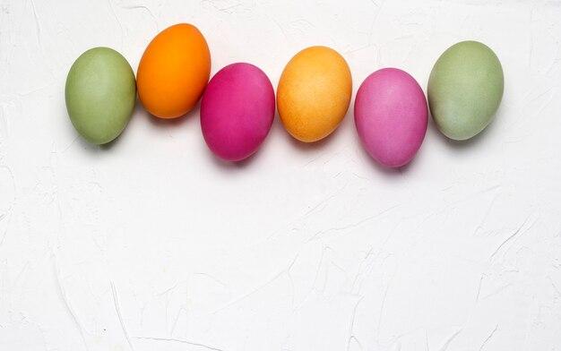 Uova di pasqua luminose su uno sfondo bianco con texture.