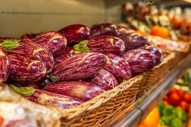 Melanzane luminose su un bancone del negozio. avvicinamento. vista laterale. vegetarismo e malnutrizione.