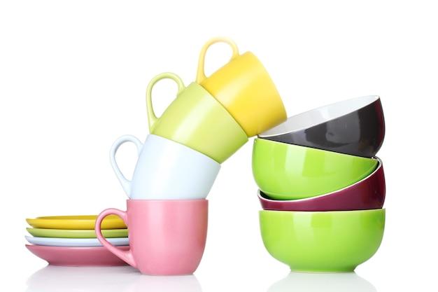 Ciotole, tazze e piatti vuoti luminosi su bianco