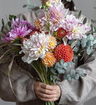 Bouquet festivo luminoso con fiori di crisato in mani femminili, il concetto di festa della donna.