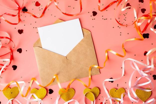 Luminoso festoso in modo piatto per qualsiasi vacanza su un muro rosa, con busta artigianale e foglio di carta bianca per il testo di saluto