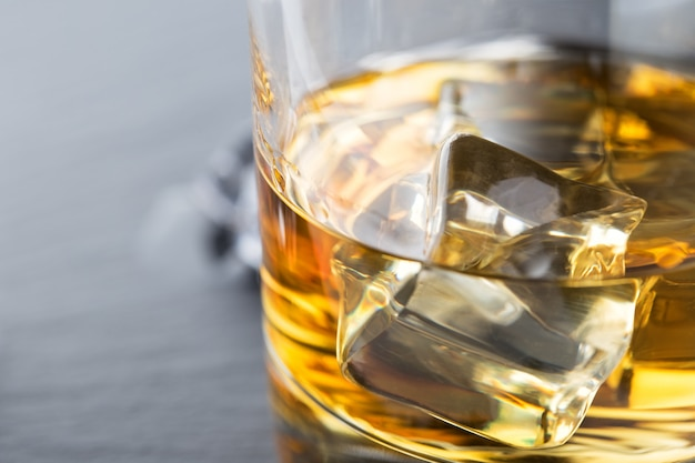 Frammento luminoso di whisky con ghiaccio in un bicchiere