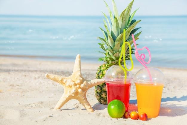 Luminoso succhi di frutta freschi, frutta, ananas, anguria, sulla sabbia contro il mare