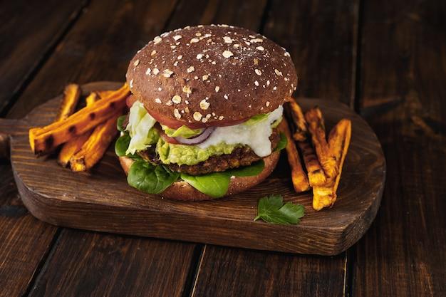 Hamburger di lenticchie luminose e sane su fondo rustico scuro