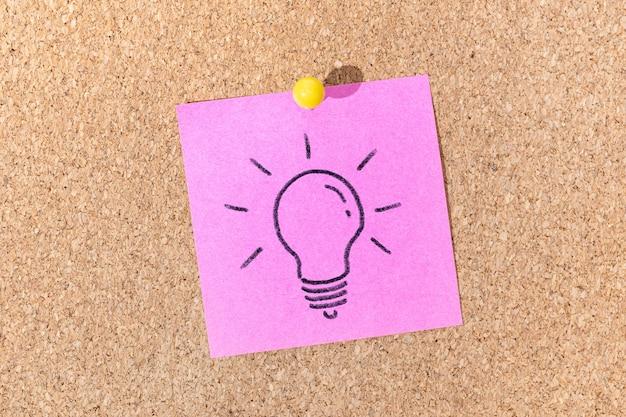 Idea brillante o concetto di processo creativo. lampadina disegno su una nota adesiva sulla bacheca di sughero