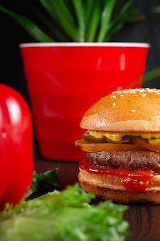 Hamburger alla griglia luminosi e succosi con manzo e formaggio cheddar. concetto di fast food
