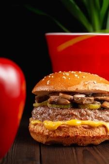 Hamburger alla griglia succosi luminosi con funghi e cetrioli marinati su fondo di legno. concetto di fast food
