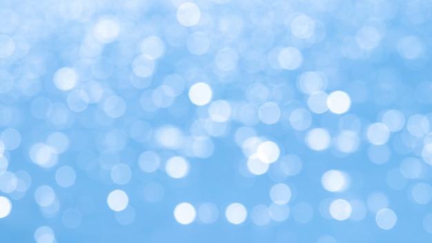 Priorità bassa astratta blu-chiaro luminosa con bokeh bianco