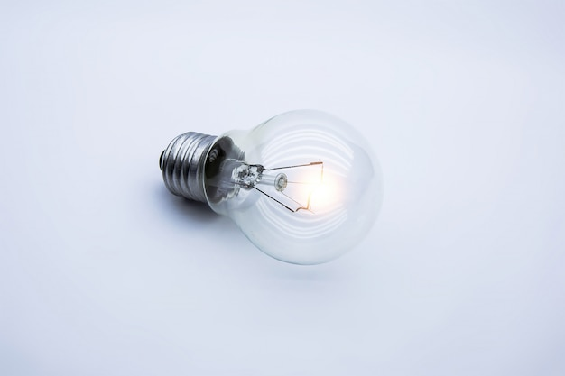 Lampadina luminosa su bianco, concetto per l'idea creativa.
