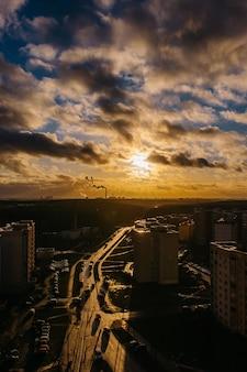 Luce intensa brilla sulla strada e sul tetto. la luce e l'ombra di un incredibile tramonto in città. fumo dal camino sullo sfondo dei raggi del sole.