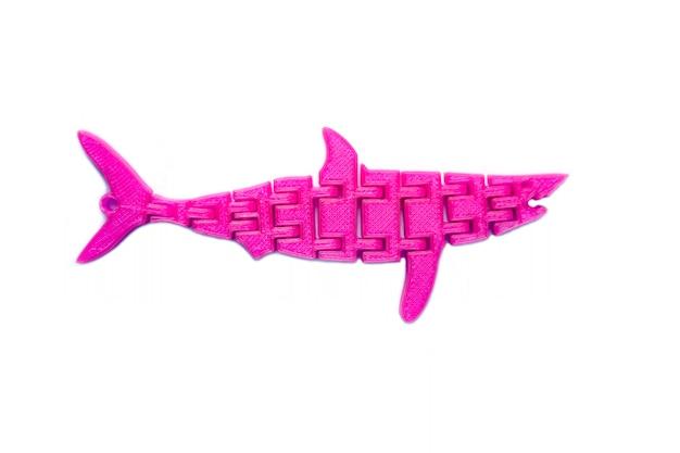 Oggetto rosa chiaro brillante a forma di giocattolo di pesce stampato su stampante 3d isolata su sfondo bianco. modellazione a deposizione fusa, fdm. concetto di moderna tecnologia additiva progressiva per la stampa 3d.