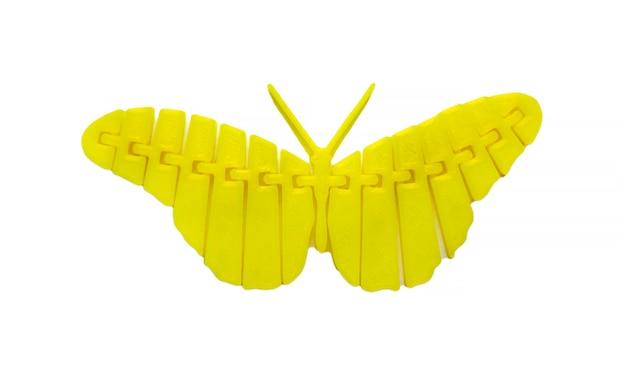 Oggetto giallo chiaro brillante a forma di farfalla giocattolo stampato su stampante 3d isolata su sfondo bianco. modellazione a deposizione fusa, fdm. concetto di moderna tecnologia additiva progressiva per la stampa 3d.