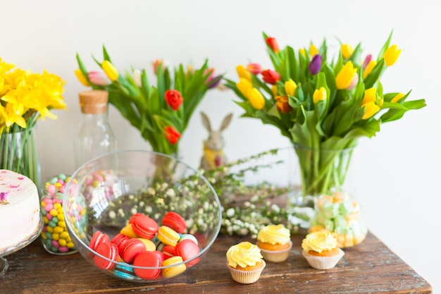 Amaretti luminosi e cupcakes su un tavolo in legno luce naturale al chiuso girato con piccola profondità di campo