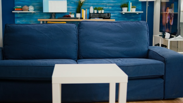 Luminoso soggiorno moderno senza nessuno con mobili e pareti blu, splendidamente decorato. arredamento moderno abbastanza semplice di un accogliente appartamento con televisione in sottofondo