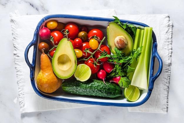 Verdure e frutta fresche multicolori luminose estive su un tavolo in una teglia. cucina, ingredienti per insalata