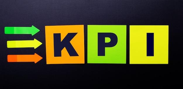 Adesivi di carta multicolori luminosi su sfondo nero con il testo kpi