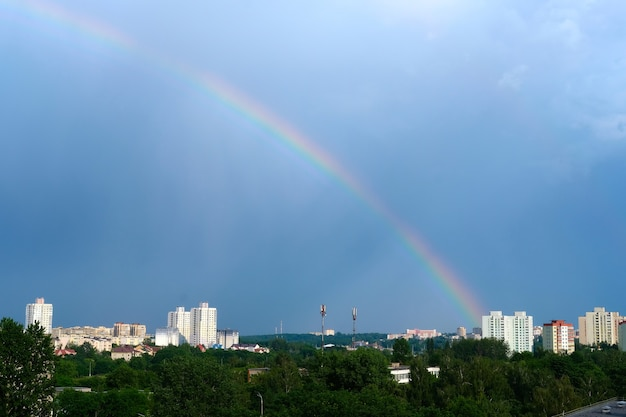 Arcobaleno multicolore luminoso sopra le case della città nel cielo blu