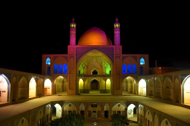 Luminosa illuminazione notturna della facciata della moschea agha bozorg a kashan