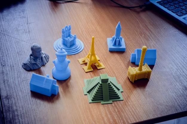 Oggetti luminosi stampati da un primo piano della stampante 3d. la stampante 3d tridimensionale automatica esegue la modellazione plastica in laboratorio. tecnologia additiva moderna e progressiva