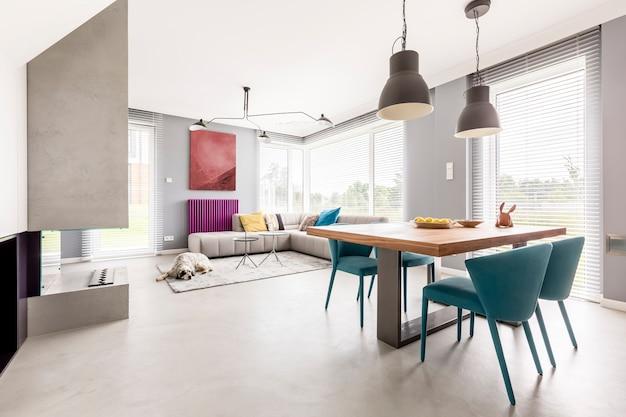 Interni luminosi di un appartamento a pianta aperta dal design moderno con tavolo comune in legno, divano beige e sedie di design blu