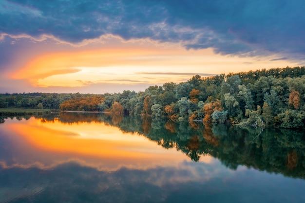 Il cielo azzurro-arancione si riflette nelle calme acque limpide del lago. fresca mattina d'estate. paesaggio pittoresco in campagna.