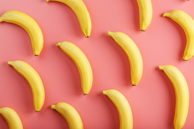 Modello luminoso di banane gialle su sfondo rosa. vista dall'alto. lay piatto. modelli di frutta