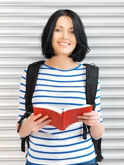 Immagine luminosa di donna attraente con borsa e libro..