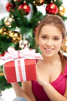 Immagine luminosa di donna felice con confezione regalo e albero di natale......