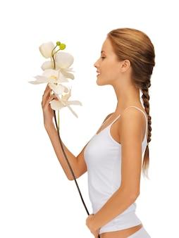 Immagine luminosa di bella donna con fiore di orchidea.