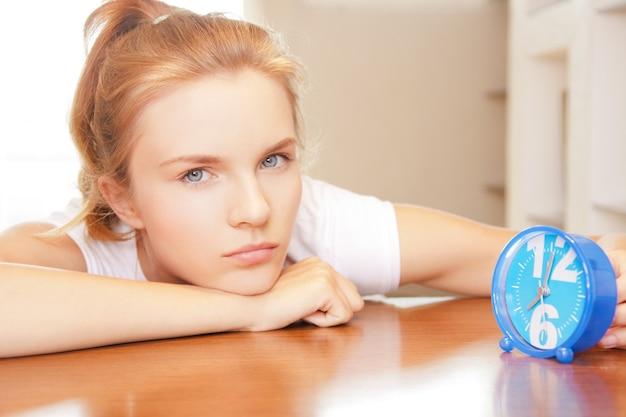 Immagine luminosa di un'adolescente pensierosa con l'orologio