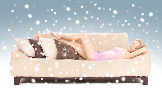 Immagine luminosa di una donna addormentata sul divano con la neve