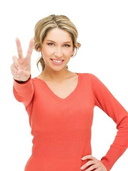 Immagine luminosa di una giovane donna che mostra il segno della vittoria