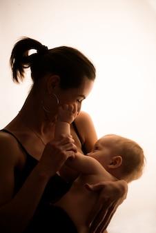 Ritratto luminoso di una mamma che allatta al seno bambino
