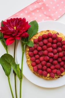 Piatto di torta di lamponi brillante e sdraiato su un tovagliolo rosa