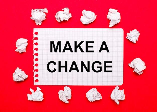 Su uno sfondo rosso brillante, fogli di carta stropicciati bianchi e un foglio di carta con il testo fare un cambiamento