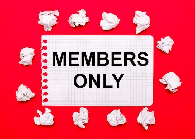 Su uno sfondo rosso brillante, fogli di carta stropicciati bianchi e un foglio di carta con il testo solo membri