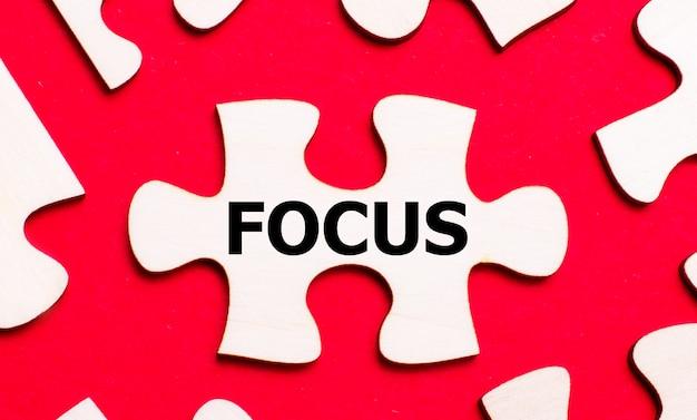 Su uno sfondo rosso brillante, puzzle bianchi. in uno dei pezzi del puzzle, il testo focus