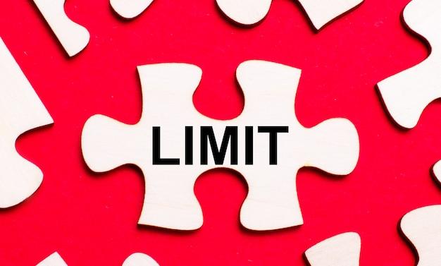 Su uno sfondo rosso brillante, puzzle bianchi. in uno dei pezzi del puzzle, il testo limit