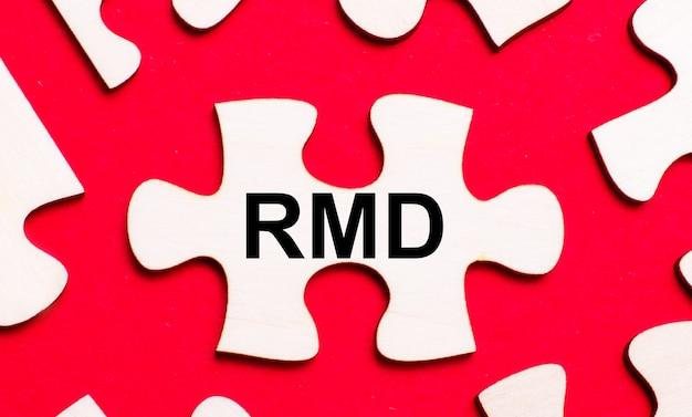 Su uno sfondo rosso brillante, puzzle bianchi. in uno dei pezzi del puzzle, il testo rmd required minimum distributions