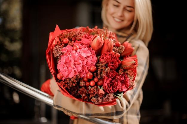 Mazzo rosso luminoso dei fiori in mani della donna
